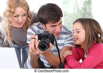 Family looking at pictures on camera screen