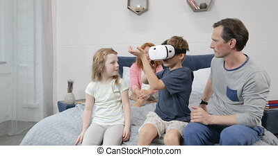 Family Looking At Son Play Games Wearing Virtual Reality Glasses In Bedroom, Parents And Children Spend Morning Together At Home