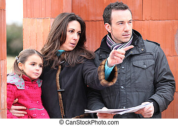 family looking at the plan of their future house