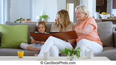 Family looking photo album in living room 4k - Family ...