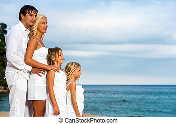 Family lookinh into the distance on beach.