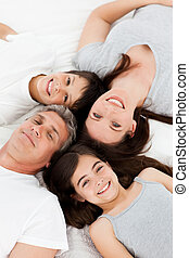 Family  lying down on their bed