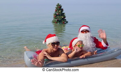 Family lying in surf on sand beach against Christmas tree in water waving hands