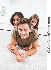 Family lying on a carpet posing