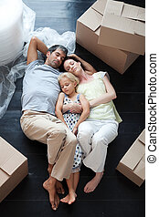 Family lying on floor after buying house