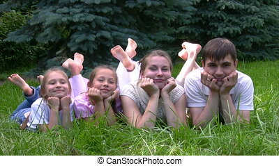 family lying on grass and dangles crossed legs in park