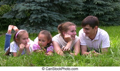 family lying on grass and talks in park
