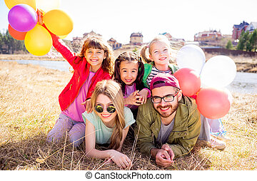 Family lying on grass with balloons