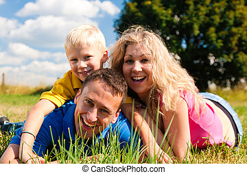 Family lying on meadow