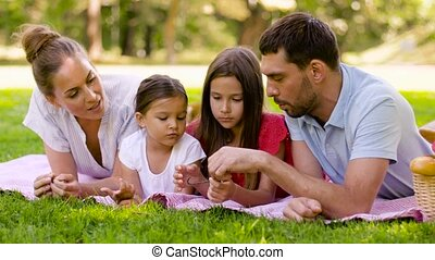 family, leisure and people concept - happy mother, father and two daughters with twigs lying on picnic blanket and talking in summer park