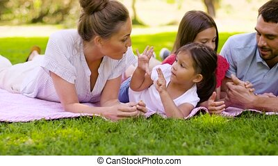 family, leisure and people concept - happy mother, father and two daughters lying on picnic blanket and talking in summer park