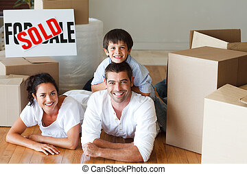 Family lying on the floor with boxes