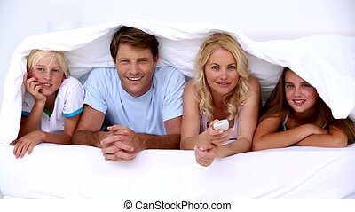 Family lying under the covers watching tv at home in bed