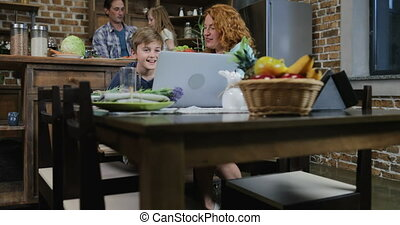 Family Make Video Call Using Laptop While Siiting At Table In Kitchen Happy Parents And Children Waving Hands