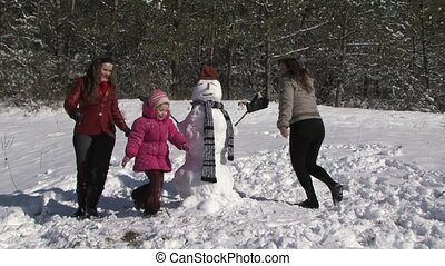 Family making a snowman together.