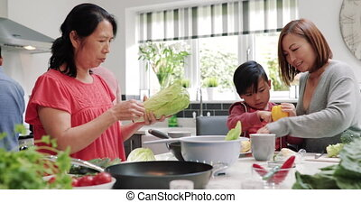 Family Making a Stir Fry Together - Three generation family...