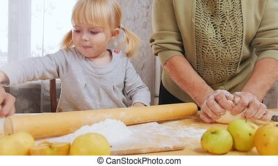 Family making little pies. A little girl roll out the dough....