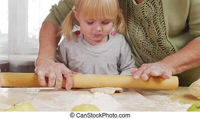 Family making little pies. A little girl roll out the dough...