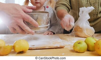 Family making little pies. Sifting flour. Little girl looking
