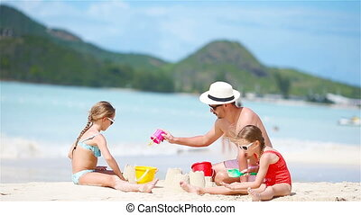 Family making sand castle at tropical white beach. - Family...