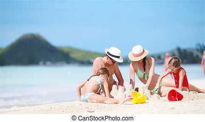 Family making sand castle on white beach on summer holidays...