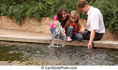family making water splash near pound - Happy family with...