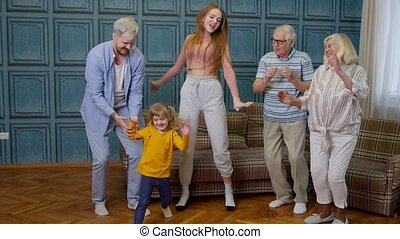 Family members of different generations having fun listening music, dancing crazy in room at home