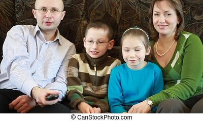 Family members sitting on couch and pass each other broken remote control