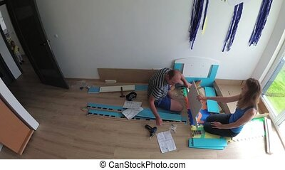Family mom and dad assembly new bed for toddler boy in his room. Timelapse