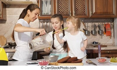 Family, mom and daughters are cooking cream for cake and...