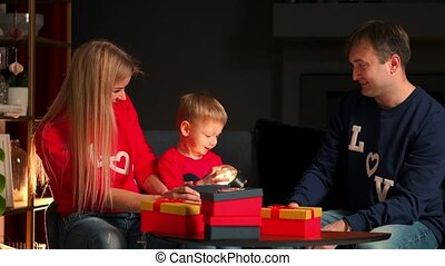 Family mom dad and son at Christmas open gifts at home sitting on the couch in the Christmas interior. Warm and cozy home atmosphere