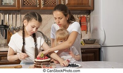 Family, mom with two little daughters are decorating birthday cake with berries together in kitchen at home.