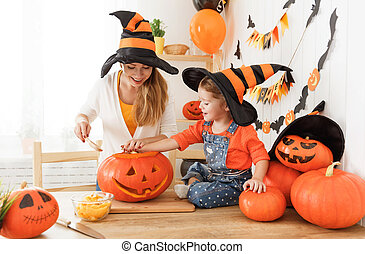 family mother and child daughter in hat witch are preparing for Halloween carve a pumpkin