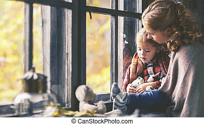 family mother and child daughter look out window on rainy autumn day