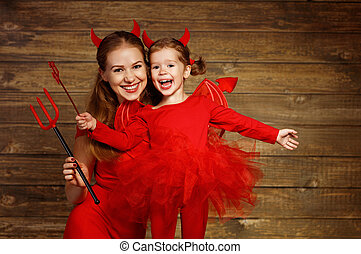 Family mother and child daughter celebrate Halloween in devil costume