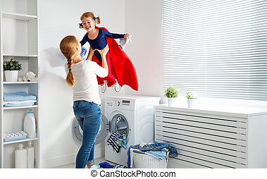 family mother and child girl little superhero helper in laundry