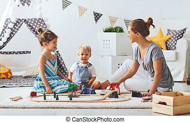 family mother and children play a toy railway in playroom - ...