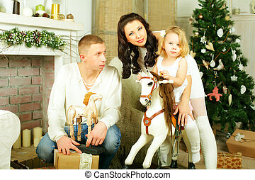 Family, mother, father and child with old toy horse, new year eve