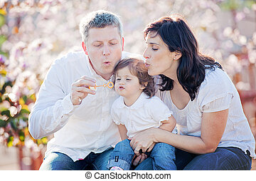 family, mother father and daughter blowing bubbles