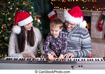 Family - mother, father and kid wearing santa hats playing the piano over christmas background
