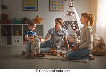 family mother father and   son playing together in children's playroom