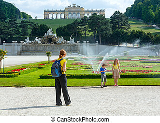 Family (mother with children) in summer park and Gloriette on hill top (Schonbrunn Palace Garden, Vienna, Austria). All another people are unrecognizable