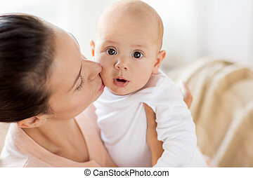 happy mother kissing little baby boy at home