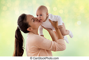 happy mother kissing little baby boy over green