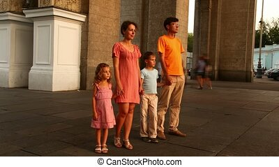 Family motionlessly stay in city, people are around carried by