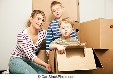 Family moving in their new house. The sons are sitting...