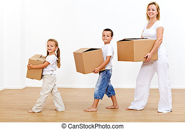 Family moving in to a new home carrying cardboard boxes