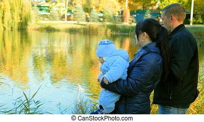 family near a pond with ducks