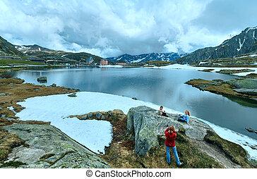 Family near Alps mountain lake