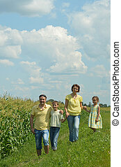 Family near field - happy nise family standing near corn...